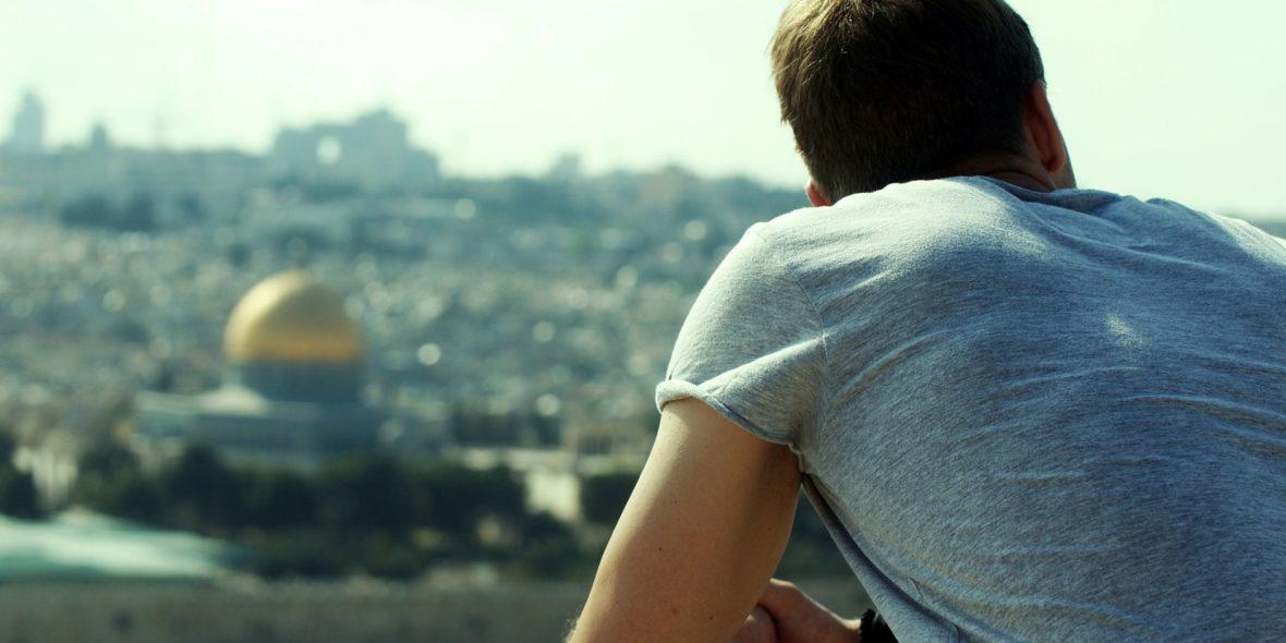 Mann blickt sitzend über Jerusalem-Panorama